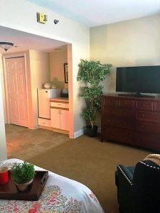 Charter Senior Living of Edgewood studio apartment with television and mini fridge